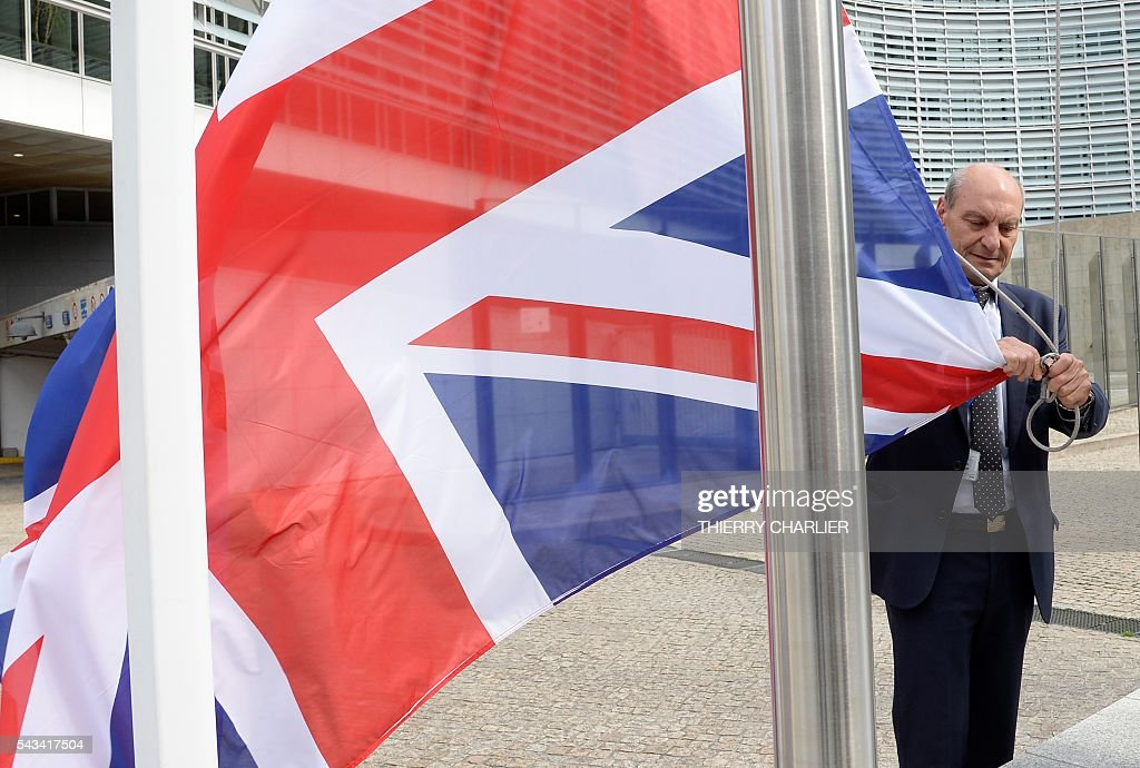 A member of the Commission removes a British flag during a European Summit at the EU headquarters in Brussels on June 28, 2016. / AFP / THIERRY