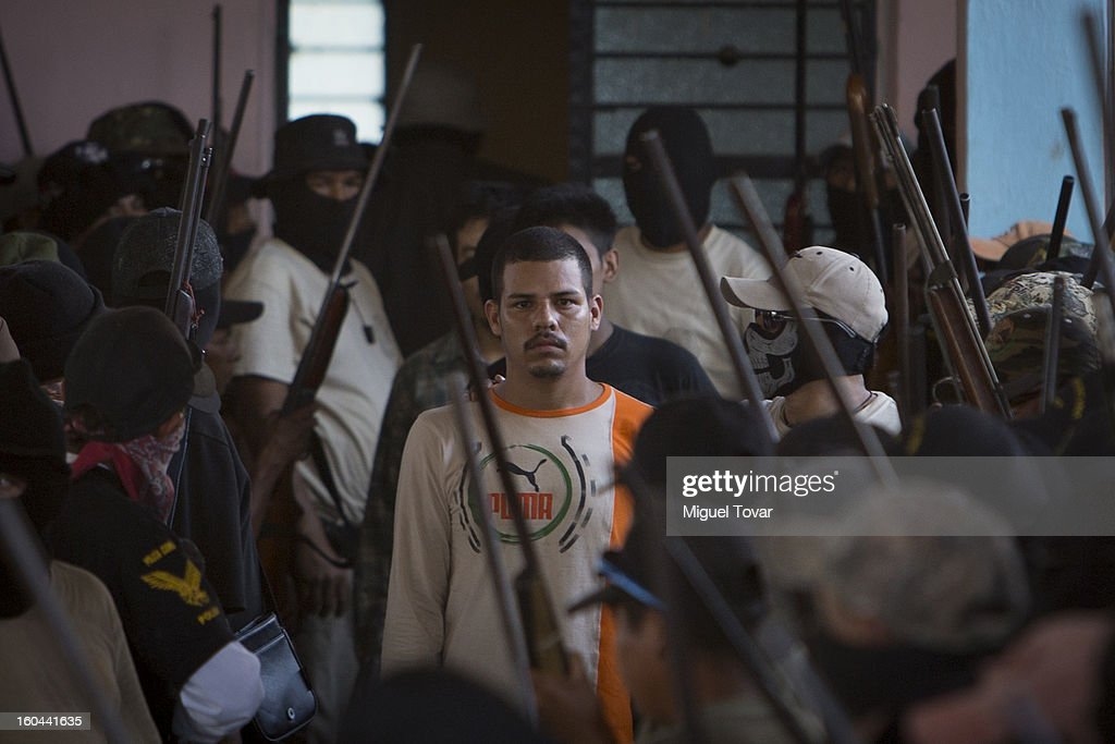 A member of the community of Ayutla escorts a kidnapping suspect on January 30, 2013 in Ayutla Guerrero, Mexico. Hundreds of men have taken up arms in several towns of the southern state of Guerrero to defend their communities against violent criminal gangs.