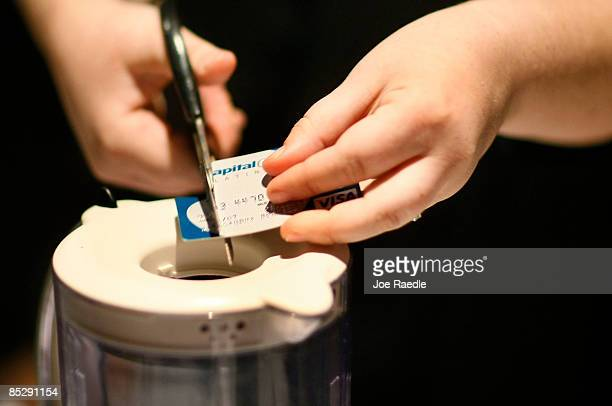 A member of the congregation cuts her credit card up to be placed in a blender as she tries to dig herself out of credit card debt during a sermon by...