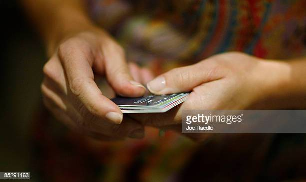 A member of the congregation prepares her credit cards to be cut up by a saw as she tries to dig herself out of credit card debt during a sermon by...