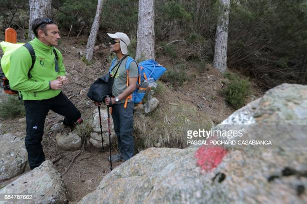 Member of the Corsica Regional Parc in charge of the GR 20 trek signing Jean Antonelli speaks with a tourist on the GR 20 near the Bavella picks...