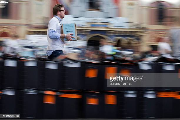 A member of the counting staff carries a selaed ballot box containing voting slips ahead of processing and counting at a count centre in north London...