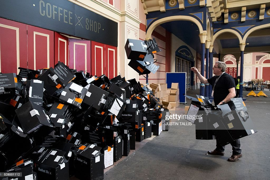 A member of the counting staff tosses empty ballot boxes onto a pile after emptying the ballot papers at a count centre in north London on May 6, 2016. Early results Friday from British local and regional elections seen as a key test for opposition Labour leader Jeremy Corbyn showed strong gains for Scottish nationalists, as London looked set to elect its first Muslim mayor. London was on track to become the first EU capital with a Muslim mayor as voters went to the polls Thursday after a bitter campaign between Prime Minister David Cameron's Conservatives and the opposition Labour party. / AFP / JUSTIN