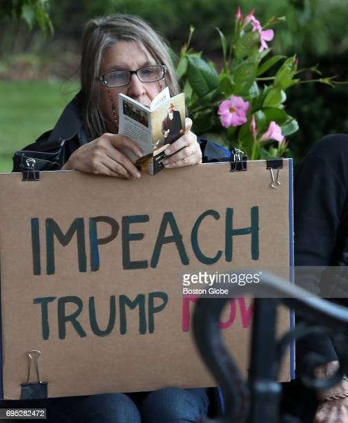 A member of the crowd holds a sign and reads a pocket version of the US Constitution during a rally outside of Newton City Hall in Newton MA held by...