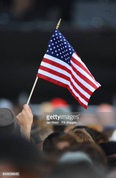 A member of the crowd waves an American flag as Bruce Springsteen and the E Street Band perform on stage at Hard Rock Calling in Hyde Park in London