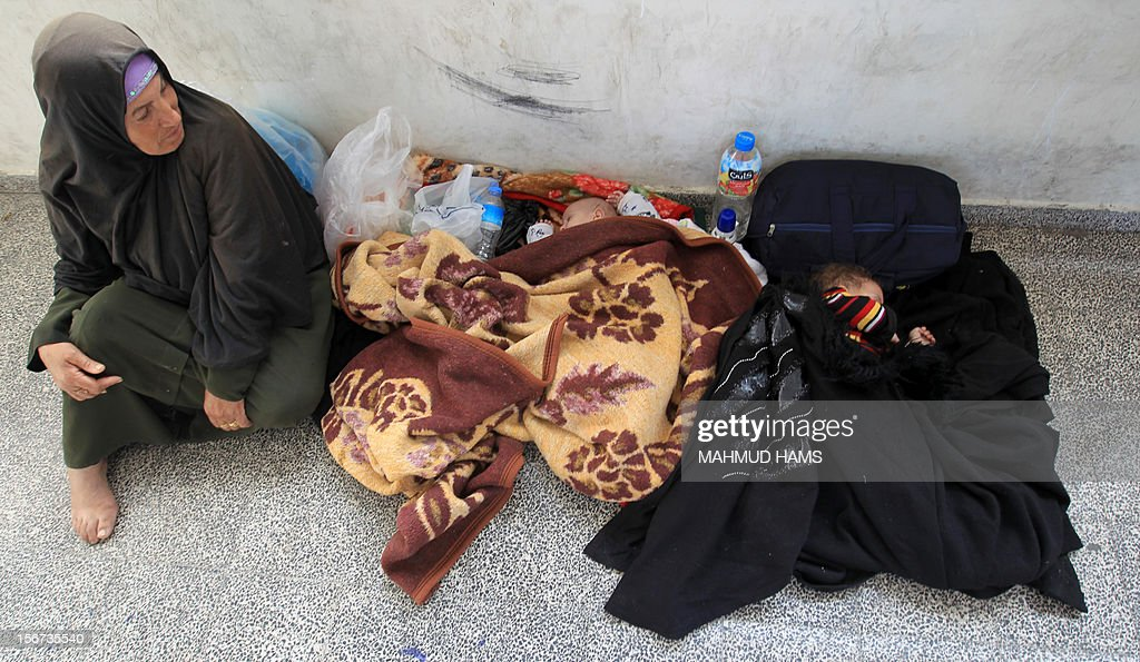 A member of the displaced Palestinian al-Attar family, who fled their house, sits on the ground next to two sleeping babies, in a classroom at a United Nations-run school, where they have take n shelter in Gaza City on November 20, 2012. Israeli leaders discussed an Egyptian plan for a truce with Gaza's ruling Hamas, reports said, before a mission by the UN chief to Jerusalem and as the toll from Israeli raids on Gaza rose over 100. AFP PHOTO/MAHMUD HAMS