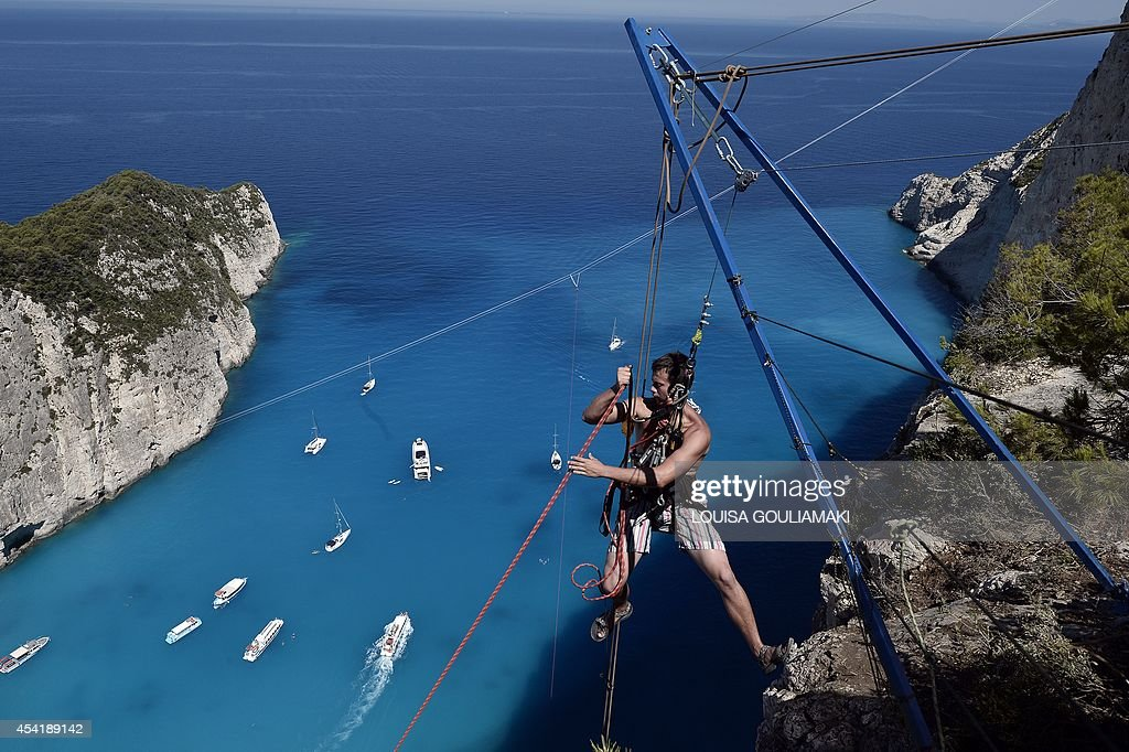 A member of the ' dream walker' team climbs up after jumping from atop the rugged rocks overlooking the azure waters of Navagio beach, one of the Greece's most renowned leisure spots on the popular tourist island of Zakynthos on June 23, 2014. This is rope jumping -- part diving, part rock climbing, with a touch of engineering. The aim of the project is to dream jump in 80 places with most ravishing nature and architecture all over the world .They plan to stage their next leaps at a cave complex in Croatia, a French viaduct, skyscrapers in Las Vegas and Johannesburg, and the Grand Canyon.