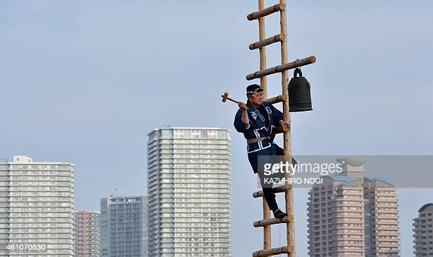 A member of the Edo Firemanship Preservation Association wearing traditional Japanese firefighting uniform hits a fire bell while performing ladder...