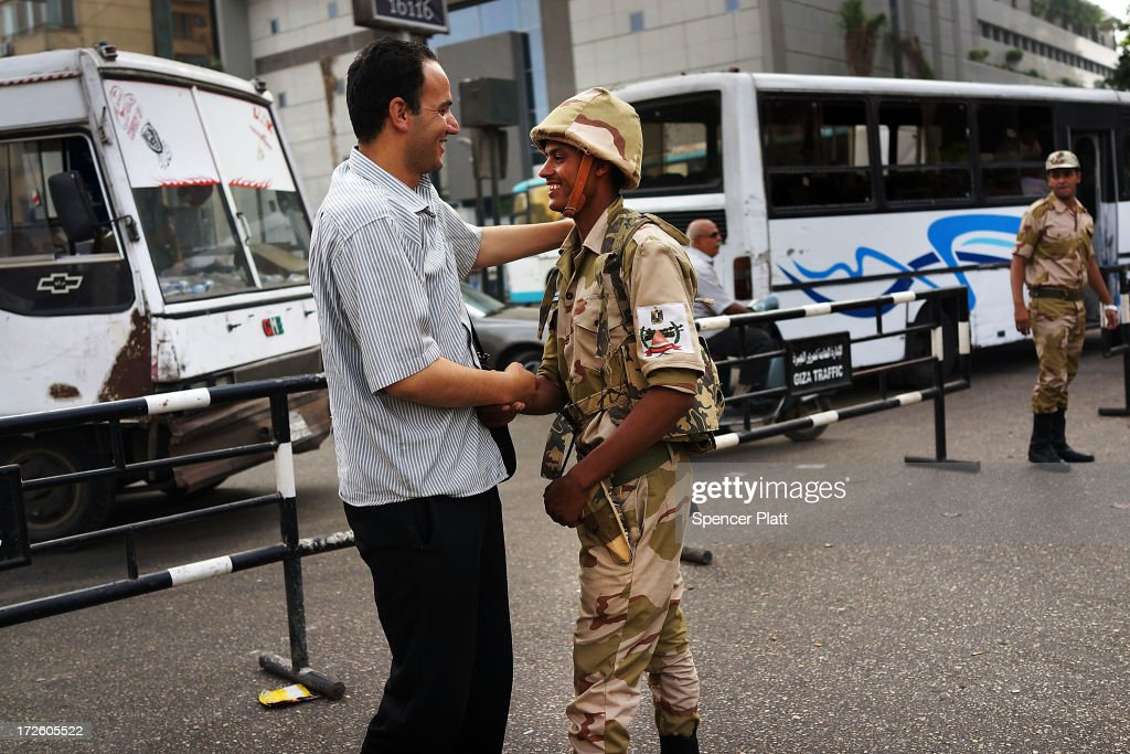 A member of the Egyptian military is greeted in support by a pedestrian in the district of Giza the morning after the first democratically elected President Mohammed Morsi was ousted from power and put under house arrest on July 4, 2013 in Cairo, Egypt. Adly Mansour has been sworn in as the interim head of state as unrest continues to spread throughout the country. Since Sunday there have been approximatley 50 deaths.