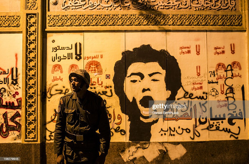 A member of the Egyptian presidential guard stands in front of a graffiti ridden wall of the presidential palace on December 12, 2012 in Cairo, Egypt. Anti-Morsi protesters were quiet after a week of continued demonstrations across Egypt against the country's draft constitution, rushed through parliament in an overnight session on November 29. The country's new draft constitution, passed by a constitutional assembly dominated by Islamists, will go to a referendum on December 15.