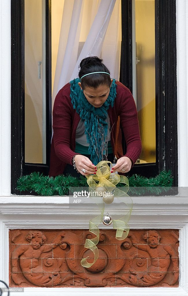 A member of the embassy staff hangs Christmas decorations from the window ahead of Wikileaks founder Julian Assange speech to members of the media and supporters from the window of the Ecuadorian embassy in Knightsbridge, west London on December 20, 2012. WikiLeaks founder Julian Assange marked six months holed up in Ecuador's embassy in London on December 19, 2012, with no end in sight to a diplomatic stand-off that has even dragged in pop icon Lady Gaga. AFP PHOTO/Leon Neal
