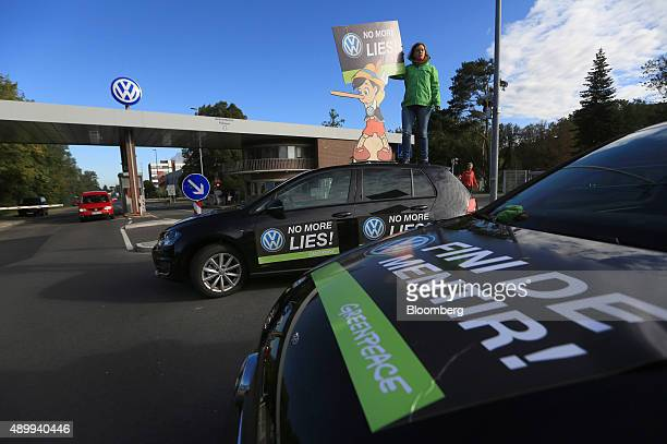 A member of the environmental action group Greenpeace holds up a Pinocchio placard during a protest outside the Volkswagen AG headquarters in...