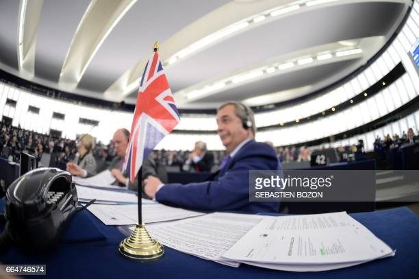 Member of the European Parliament and former leader of the antiEU UK Independence Party Nigel Farage sits next to a Union Jack flag at the European...