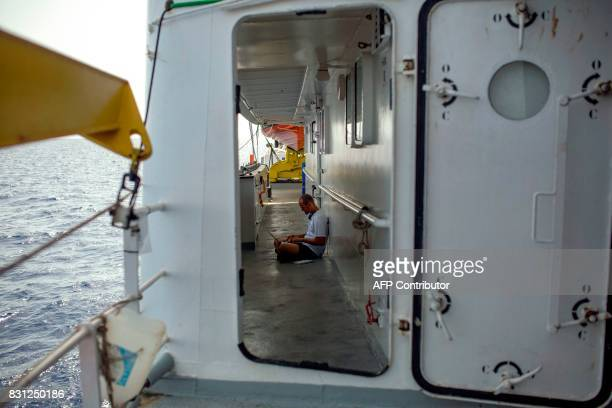 A member of the European search and rescue association 'SOS Mediterranee' works on his laptop aboard the Aquarius rescue ship on August 14 2017 in...