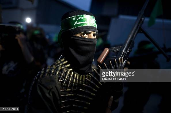 TOPSHOT A member of the Ezzedine alQassam Brigades the military wing of the Palestinian Islamist movement Hamas holds his weapon during a rally on...