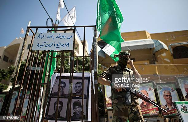A member of the Ezzedine alQassam Brigades the military wing of the Palestinian Islamist movement Hamas stands next to mock jails during a rally...