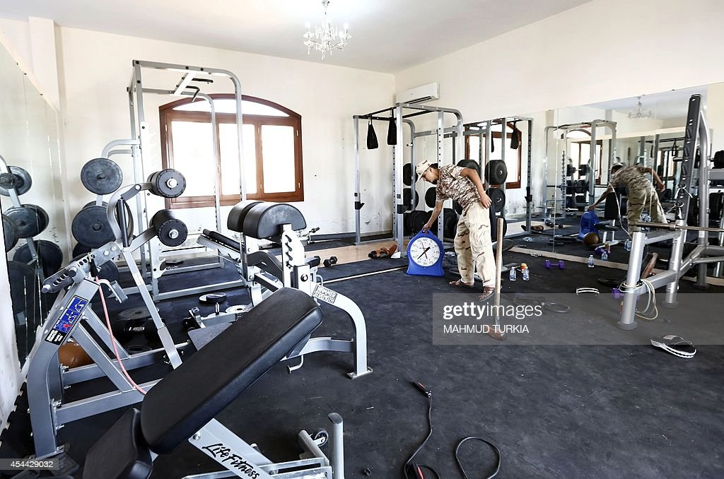 A member of the Fajr Libya Islamist militia stands at the gym of a villa at the US diplomatic compound in the Libyan capital Tripoli on August 31...
