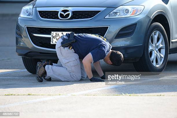 A member of the FBI Evidence Response Team gathers evidence at the scene of a shooting in the parking lot of the Armed Forces Career Center/National...