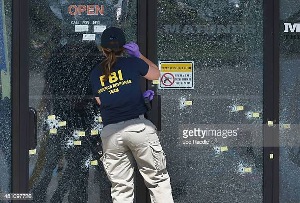 A member of the FBI Evidence Response Team looks at the bullet riddled doors as she investigates the shooting at the Armed Forces Career...