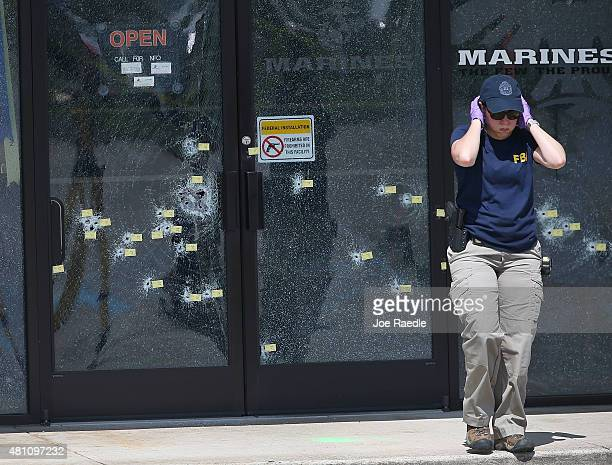 A member of the FBI Evidence Response Team walks away from the bullet riddled doors as she investigates the shooting at the Armed Forces Career...