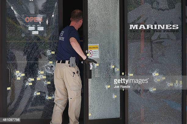 A member of the FBI Evidence Response Team walks through a bullet riddled door as he investigates the shooting at the Armed Forces Career...