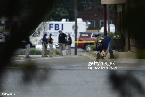 A member of the FBI inspects the crime scene after a shooting during a practice of the Republican congressional baseball at Eugene Simpson Statium...