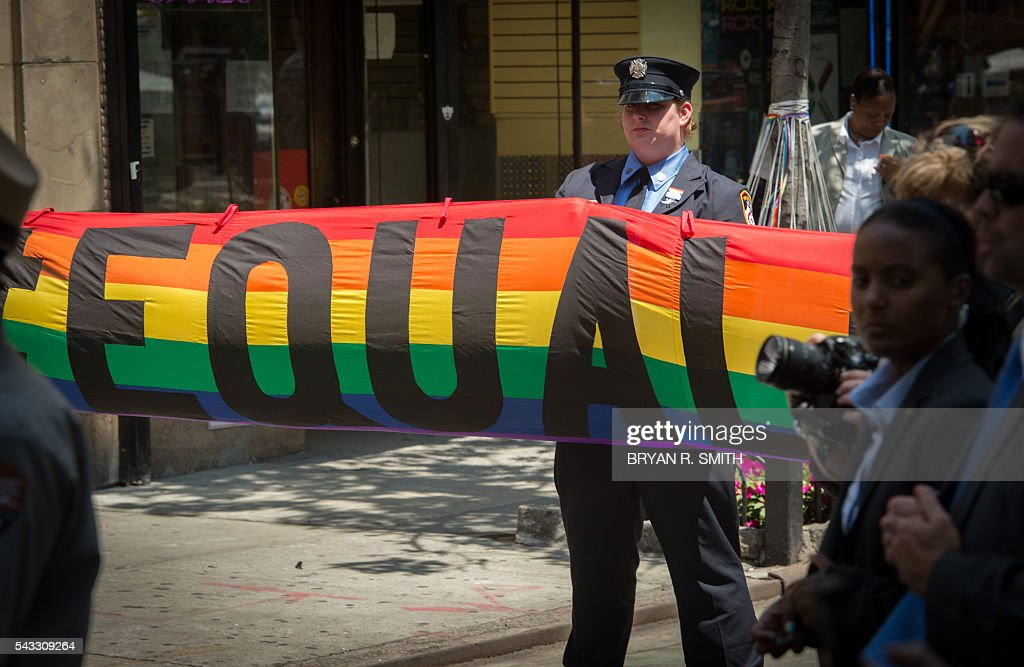 A member of the FDNY holds a banner as NY Mayor Bill de Blasio joins elected officials, advocates and New Yorkers in designating Stonewall Inn a National Monument,on June 27, 2016 in New York. / AFP / Bryan R. Smith