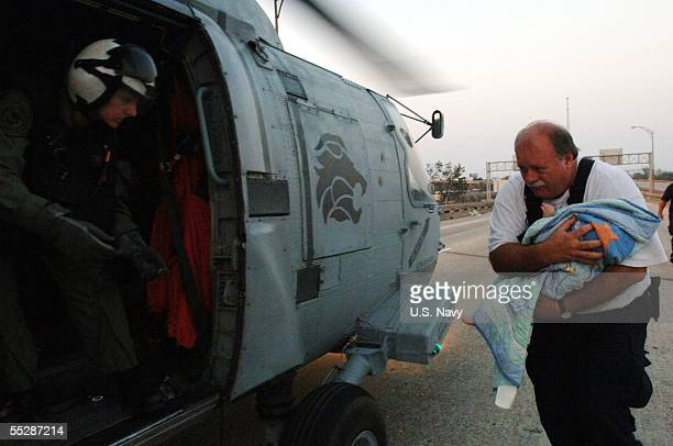 A member of the Federal Emergency Management Agency Urban Search and Rescue Task Force rushes a baby to a Navy air crewman during an evacuation...