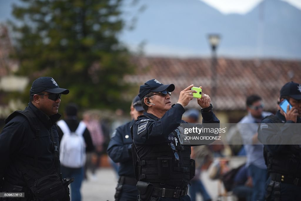 A member of the Federal Police takes pictures of the cathedral of San Cristobal de las Casas, Chiapas State, Mexico on February 12, 2016. Pope Francis will arrive in Mexico on Friday, where he will visit until February 17. AFP PHOTO/Johan ORDONEZ / AFP / JOHAN ORDONEZ