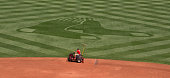 A member of the Fenway Park grounds crew drives a machine across the infield before a game between the Boston Red Sox and the Houston Astros at...