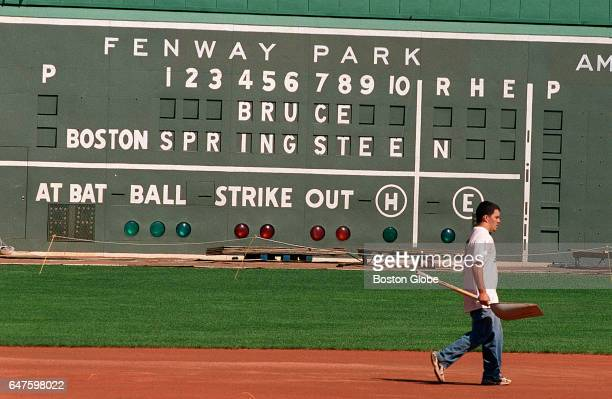 A member of the Fenway Park grounds crew walks towards second base after tamping down area around third base while the temporary stage for the...