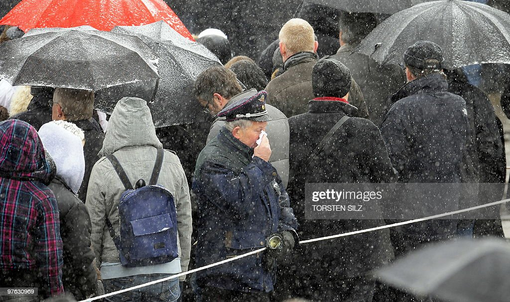 A member of the fire brigade weeps as people shelter from the snow under umbrellas during a memorial service marking the first anniversary of the shooting at the Albertville secondary school in Winnenden, southern Germany on March 11, 2010. A year ago 17-year-old teenager Tim K. used his father's pistol to kill 15 people at the school before killing himself.