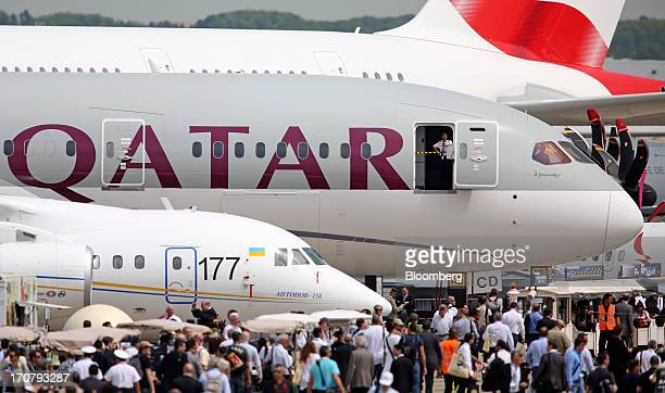 A member of the flight crew looks out from the cabin door of a Boeing Co 787 Dreamliner aircraft operated by Qatar Airways Ltd on the second day of...