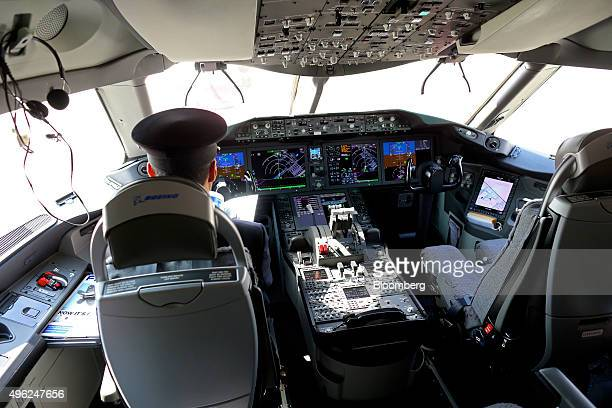 A member of the flight crew sits in the cockpit of a Boeing Co 787 Dreamliner operated by Qatar Airways Ltd on the opening day of the 14th Dubai Air...