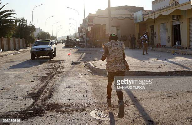 TOPSHOT A member of the forces loyal to Libya's UNbacked Government of National Accord runs on a street on August 21 2016 near the central area known...