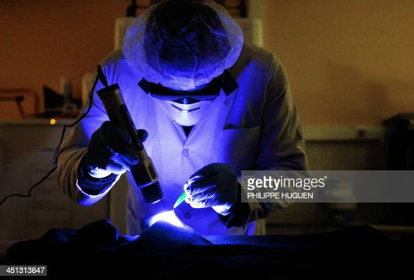A member of the forensic section of the French gendarmerie uses a UV lamp as he looks for evidence on a garment in a laboratory of the gendarmerie in...