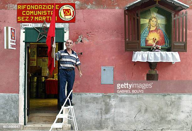 A member of the former Italian Communist Party brandishes 01 September 2002 the party's red flag next to Catholic shrine featuring Jesus Christ at...