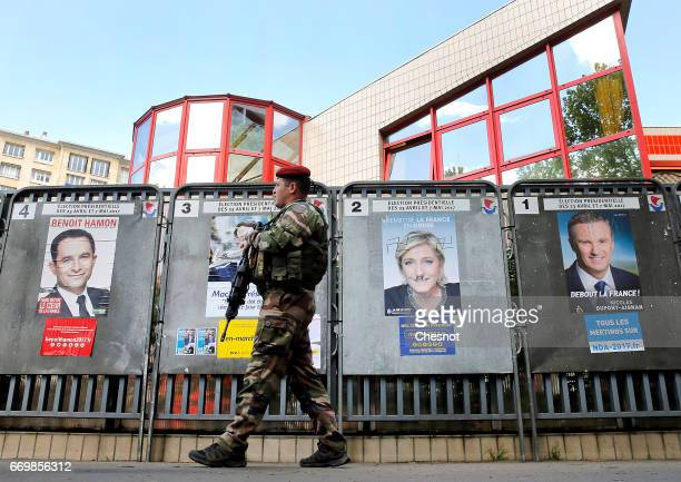 A member of the French army walks on patrol in front of official campaign posters of candidates who runs in the 2017 French presidential election on...