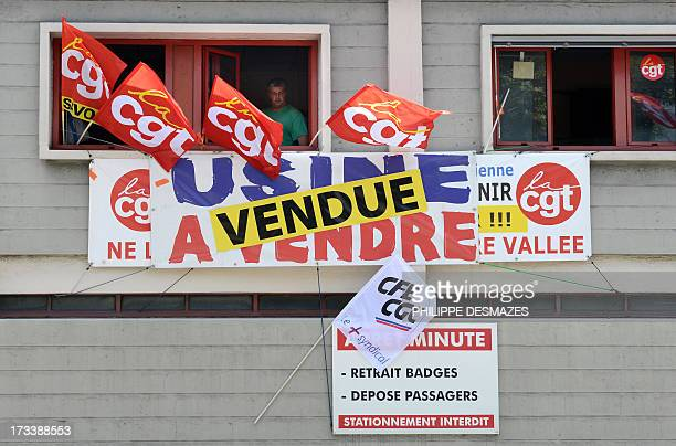 A member of the French CGT union stands in a window with CGT flags and banner which reads 'Factory on sale' and 'Factory sold' at the Rio Tinto Alcan...