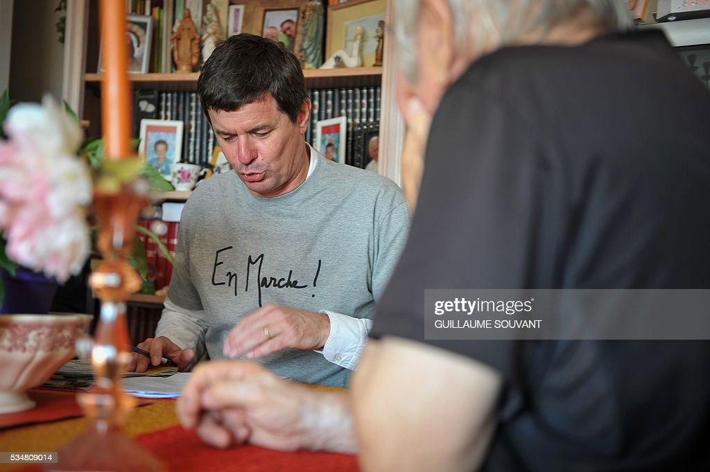 A member of the French Economy minister Emmanuel Macron's political movement 'En Marche' (On the Move) speaks to a man at his home during a door-to-door campaign on May 28, 2016 in Tours, central France. Militants wear a tee-shirt reading 'En Marche' (On the Move). SOUVANT