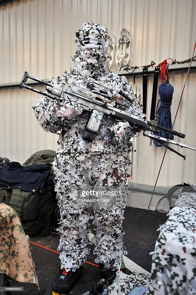 A member of the French special forces in camouflaged battle dress waits for French Defence Minister prior to his visit to a sniper commando base on January 18, 2013 in the northwestern French town of Lanester. AFP PHOTO / FRANK PERRY