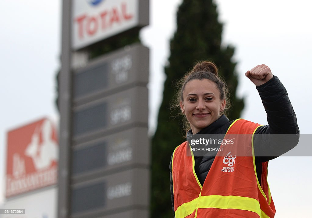 A member of the French union the CGT makes a fist as members block the entrance of an industrial zone as they protest against the labour law reforms on May 26, 2016 in Vitrolles in southern France. France faced fresh strikes after nuclear power station workers voted to join gathering protests against labour law reforms that have forced the country to dip into strategic fuel reserves due to refinery blockades. Protesters are furious that the government rammed the labour market reforms through parliament without a vote, which are designed to address France's famously rigid labour market by making it easier to hire and fire workers. / AFP / BORIS