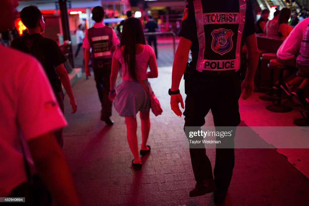 A member of the FTPA escorts a Cambodian woman to the mobile headquarters on Pattaya's Walking Street on July 31, 2014 in Pattaya, Thailand. Since 2002, members of the Foreign Tourist Police Assistants (FTPA) of Pattaya have been assisting local police on Walking Street, Pattaya's main nightlife area. Members of the FTPA carry handcuffs, batons, and pepper spray, and are charged primarily with assisting foreign visitors and the Thai police, as well as breaking up fights and catching thieves.
