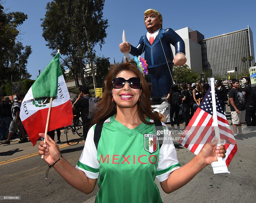 A member of the 'Full Rights for Immigrants Coalition' poses in front of a giant effigy of US Republican Party presidential hopeful Donald Trump as...