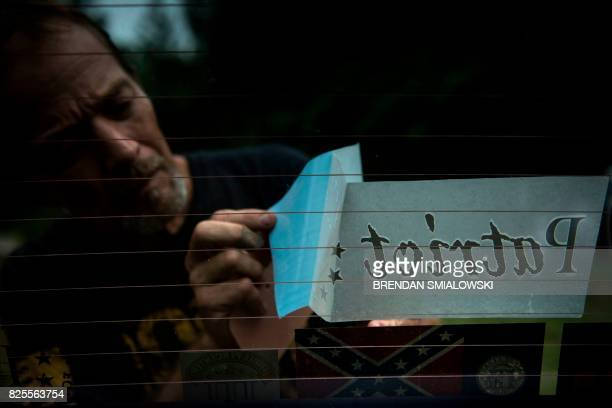 A member of the Georgia Security Force III% militia applies a decal to another member's vehicle before a field training exercise July 28 2017 in...