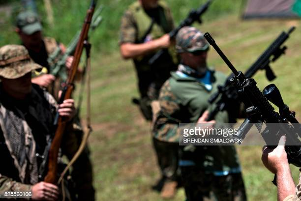 Member of the Georgia Security Force III% militia inspect their rifles before live fire training during a field training exercise July 29 2017 in...
