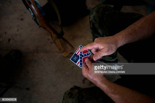 A member of the Georgia Security Force III% militia looks at a patch that combines the Confederate flag and the III% flag during a field training...