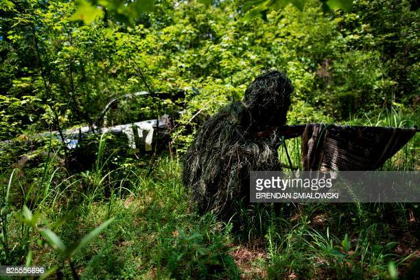 TOPSHOT A member of the Georgia Security Force III% militia wears a sniper's ghillie suit during a field training exercise July 29 2017 in Jackson...