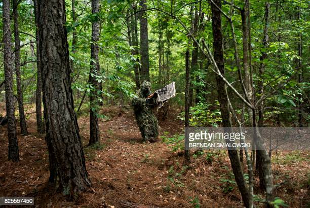A member of the Georgia Security Force III% militia wears a sniper's ghillie suit during a field training exercise July 29 2017 in Jackson Georgia /...