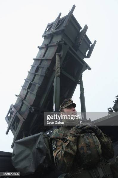 A member of the German Bundeswehr who will be sent to Turkey stands next to a Patriot missile launching system during a press day presentation at the...